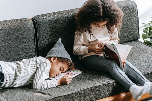 Kids studying on a sofa.
