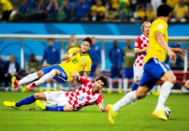 Brazilian player comes under a challenge from a Croatian in a world cup match