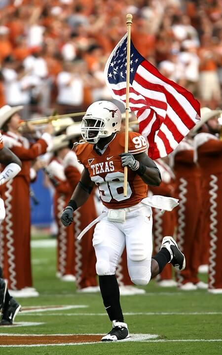 NFL player running with the US flag   DIRECTV